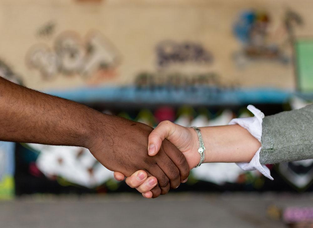 Ein dunkelhäutiger Mann gibt einer hellhäutigen Frau die Hand