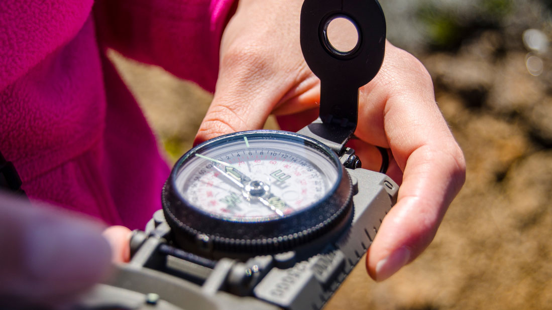 Eine Frau schaut auf einen Kompass, welchen sie in den Händen hält