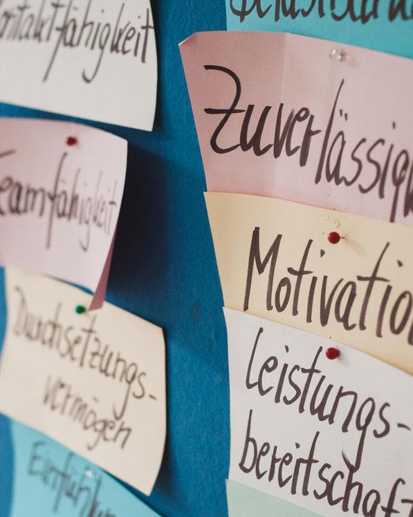 """Zettel mit den Worten """"Kontaktfähigkeit"""", """"Teamfähigkeit"""", """"Durchsetzungsvermögen"""", """"Zuverlässigkeit"""", """"Motivation"""", """"Leistungsbereitschaft"""" an einer Pinnwand"""